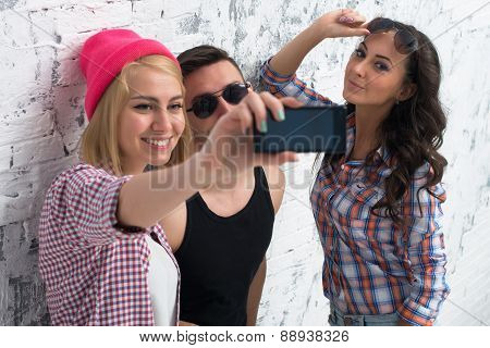 two women and man friends taking selfie together wearing summer clothes  jeans shorts jeanswear stre