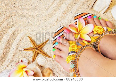 Female Feet With Pretty Multicolor Pedicure On Sand, With Frangipani Flowers And Seashells. Summerti