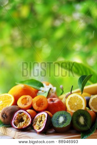 Fruits with leafs on table green background