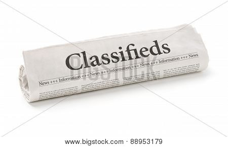 Rolled Newspaper With The Headline Classifieds