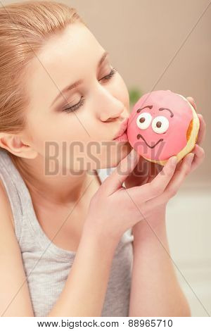 Loving sweet taste. Pretty young woman kissing a pink donut with creamy smile on it and feeling marveled about eating it poster