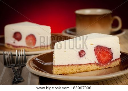 A Slice Of Delicious Cheeese Cake With Strawberries And Syrup Served On A Table