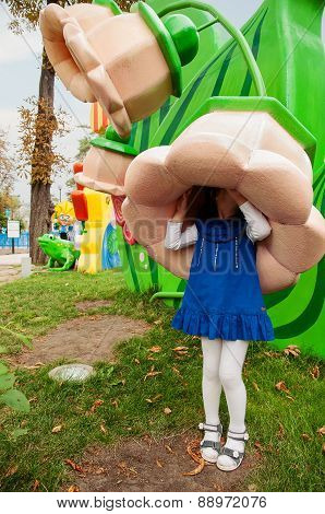 Little girl hiding under a big flower in the amusement park