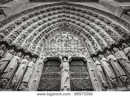 Central gothic portal of Notre Dame de Paris cathedral featuring bas relief of the Last Judgement. The heavy wooden doors are decorated by intricate iron work. The 13th century cathedral is located in the 4th arrondissement on Ile de La Cite Paris France poster