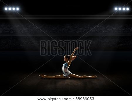 Girl engaged art gymnastic at sports hall poster