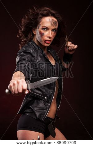 young sexy woman holding a dangerous knife in her hand