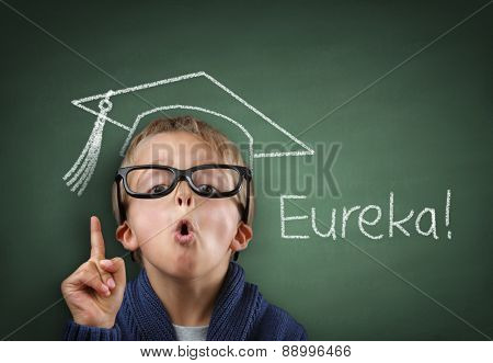 Child having a Eureka moment with mortar board drawing and Eureka on the blackboard concept for genius student, university education and future aspirations