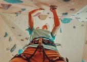 Girl in safety harness climbing artificial boulder indoors view from below poster