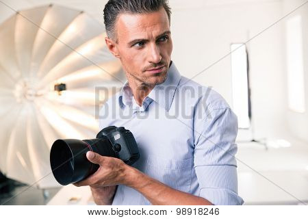 Portrait of a confident photographer holding camera and looking away in studio