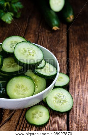 Heap of fresh sliced Cucumbers on an old wooden table poster