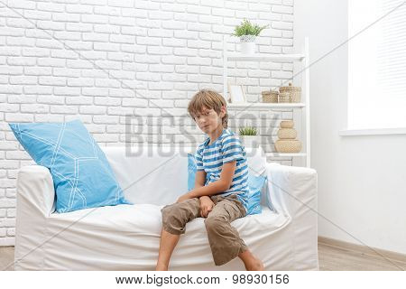 indoor portrait of young happy smiing child boy sitting on sofa at home