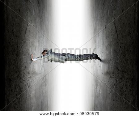 Young troubled businessman trapped between two walls poster