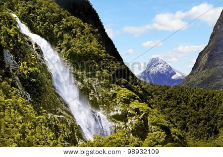 Spectacular waterfall in Milford Sound fiord New Zealand.