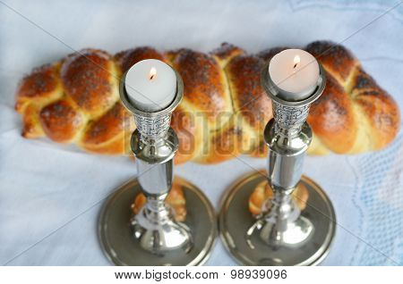Lit Shabbath candles with uncovered challah bread and kippah.