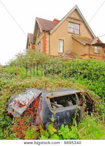 Abandoned Car Within Overgrowth By Creepy Building