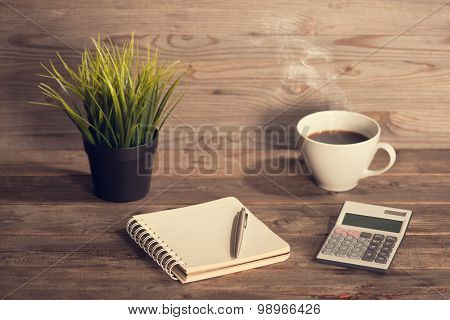 Budget analysis concept. Workplace with booklet, pen, calculator and coffee mug. Wooden table background vintage toned.