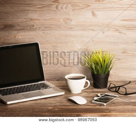 Wooden office interior, table with laptop, cup of hot coffee, mouse, glasses, smartphone, earphones and pot plant, in dramatic light vintage toned.