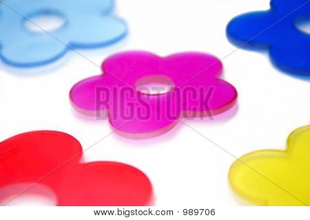 several flower shapes in blue pink red and yellow on a white refective background as an abstract. shallow depth of field with main focus on center flower. poster