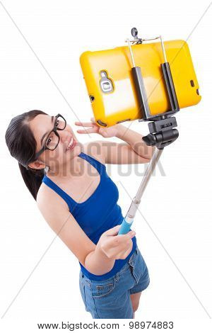 Portrait of young woman making selfie photo on smartphone with stick on a white background