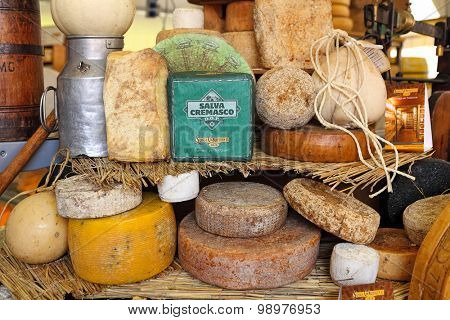 BRA, ITALY - SEPTEMBER 22, 2013: Different types of mature hard cheese on the stand. Hard cheese (granular cheese) produced by stirring and draining mixture of curd and whey and has rich tangy taste.