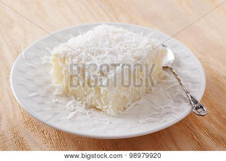 Brazilian traditional dessert: sweet couscous (tapioca) pudding (cuscuz doce) with coconut on white plate on wooden table. Selective focus poster