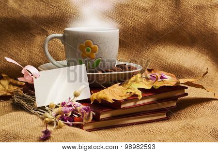 The Cup Of Coffee Lying Ot The Books With Maple Leaves
