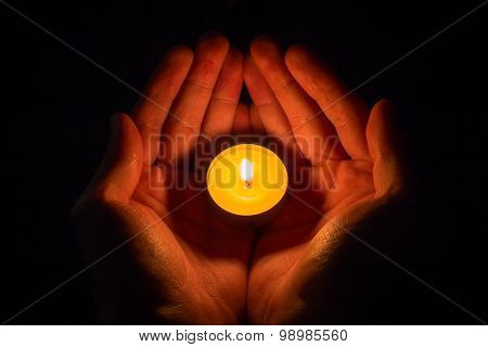 Hands In The Shape Of A Heart Holding A Lighted Candle On A Black Background