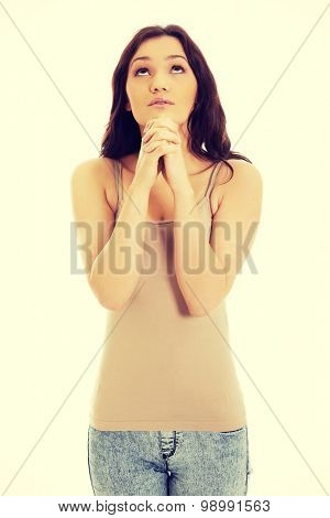 Young woman praying with her hands together and looking up.
