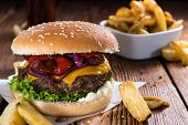Big fresh made Burger on rustic wooden background (with French Fries) poster
