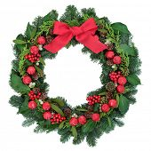 Christmas wreath with red bauble decorations and bow, holly, ivy, mistletoe and winter greenery over white background. poster