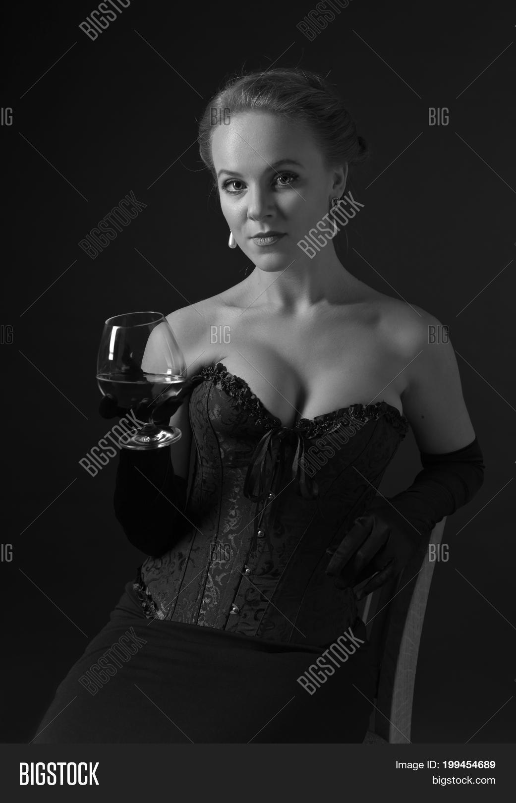 4120858a753 Portrait of young beautiful woman in black corset with glass of brandy. Beautiful blonde with perfect hair and professional make-up in retro stile .