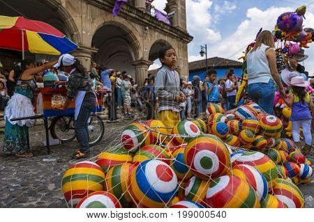 Antigua Guatemala - April 18 2014: Young girl selling colorful rubber balls in a street of the old city of Antigua in Guatemala