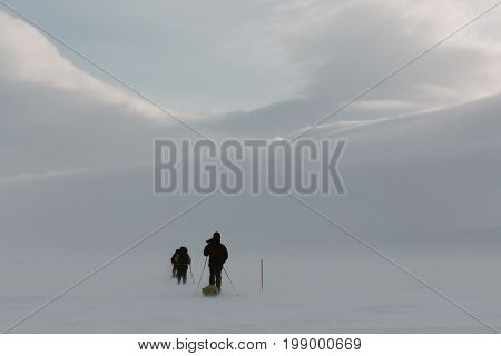 Hikers  In Backcountry Atmospheric  Frozen Remote Country In Winter