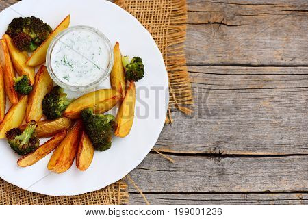 Crispy baked potatoes and broccoli with sauce on a plate and a wooden table. Baked potatoes and broccoli recipe. Vintage wooden background with copy space for text. Top view