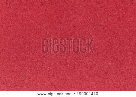Texture of old bright red paper background closeup. Structure of dense wine kraft cardboard.
