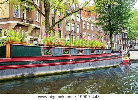 Large houseboat anchored on a canal in the capital city of Amsterdam