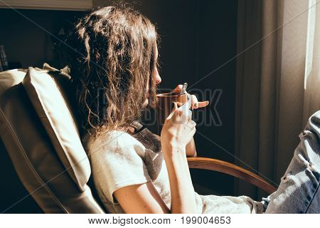 Close up portrait woman relaxing in comfortable modern chair near window in livingroom drinking tea. Warm natural light. Cozy home. Casual clothing. Room interior. Thoughtful woman. Bright sunny day