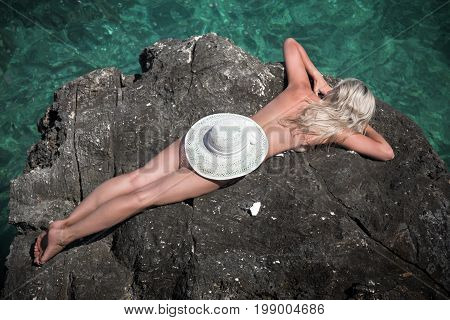 Sexy slim nude woman lays on rock outdoors with hat.