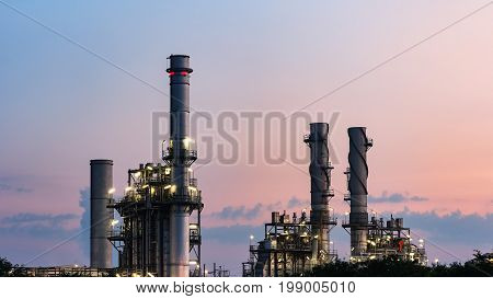 Gas turbine electrical power plant at dusk with orange sky