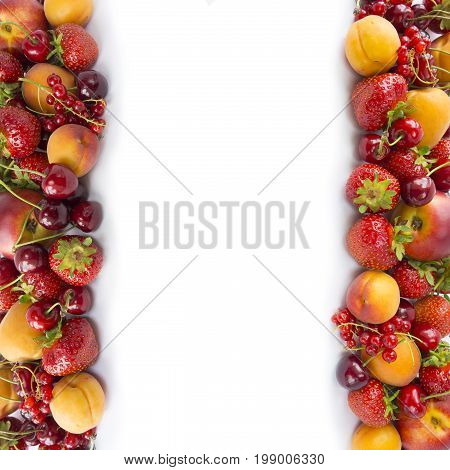 Ripe strawberries redcurrants apricots nectarines and cherries on white background. Various fresh summer berries. Top view. Berries at border of image with copy space for text. Background berries.