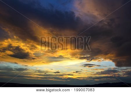 Sunset sky background. Dramatic sunset sky with evening sky clouds lit by bright sunlight - natural city sunset sky landscape view. Stunning sky clouds in the sunset. Sky landscape.Panoramic sky view.