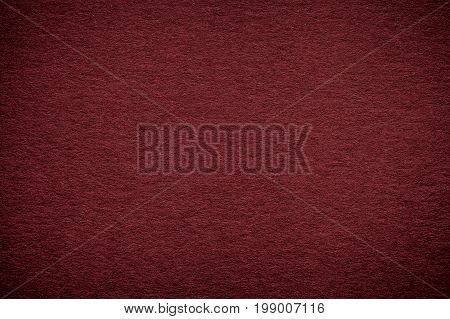 Texture of old dark red paper background closeup. Structure of dense maroon cardboard.
