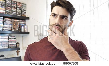 Confused or doubtful young man scratching his chin and looking up. Indoors shot in a living room
