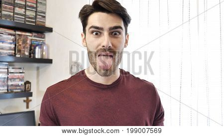 Young Man in Red Shirt Showing Funny Facial Expression with Tongue Out, Indoor at Home
