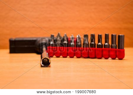 Screwdriver and nozzles on a wooden background tools for repair and dismantling