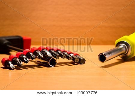 Two screwdrivers and metal nozzles on them on a wooden background tools for mounting and dismantling and also repairing
