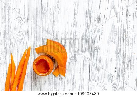 Baby food. Pumpkin puree on light wooden table background top view.