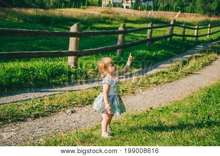 little girl stands on the country raod and point on somtheing, sunny summer day