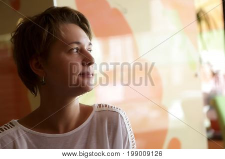 Portrait of pensive woman on a wall background