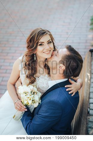 Beautiful smiling bride sits on her husband's lap and looks up